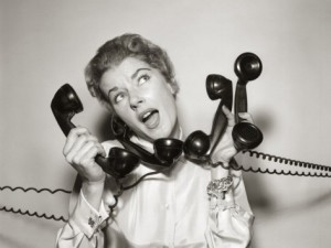 debrocke-1950s-1960s-overwhelmed-stressed-woman-answering-four-black-telephone-phone-receivers-at-one-time